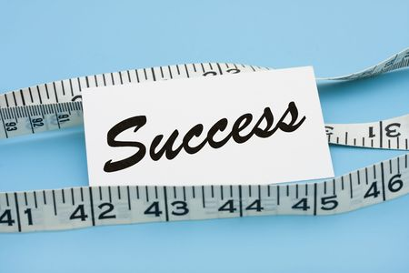 A white measuring tape with a note saying success on a blue background, measuring success Stock Photo