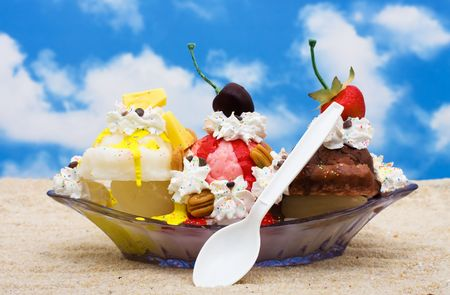 banana: A banana split ice cream sitting on sand with a sky background Stock Photo