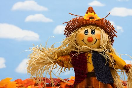 A scarecrow sitting on fall leaves on a sky background, scarecrow Stock Photo