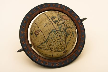 An old fashioned globe sitting on a beige background, old world