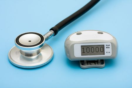 A stethoscope and a pedometer on a blue background, walking for a healthy heart photo