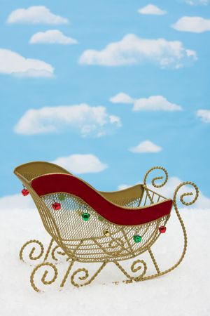 Gold metal sleigh on snow with sky background, Santa's Sleigh photo