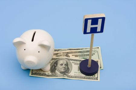 healthcare costs: A piggy bank with money and a hospital sign on a blue background, healthcare costs Stock Photo