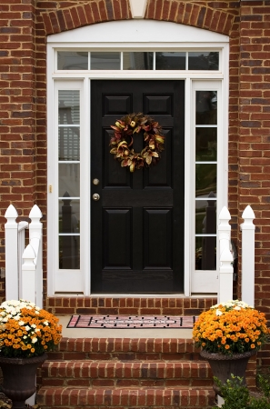 door leaf: A door on a house with a harvest wreath on it, welcome home