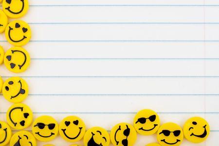 Lotes de caras sonrientes amarillo sobre un fondo de papel rayado, días felices