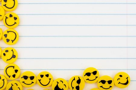 Lots of yellow smiley faces on a lined paper background, happy days Stock Photo - 5655143