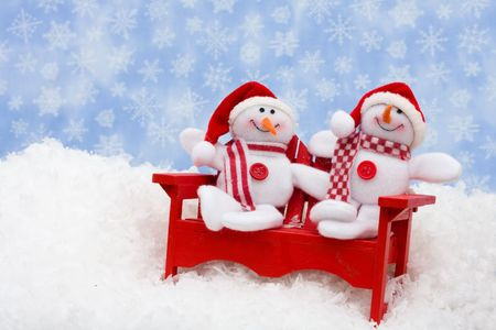 A red chair with snowmen sitting on snow with a snowflake background, happy holidays photo
