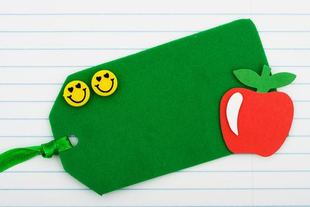 A blank gift tag sitting on lined paper background, back to school present photo