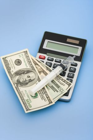 healthcare costs: A calculator with cash and a syringe on a blue background, calculating healthcare costs