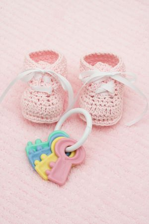 Baby booties with key rattle on a pink background, baby booties