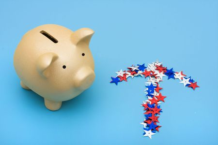 Piggy bank with multi coloured stars making an arrow on blue background, piggy bank, photo