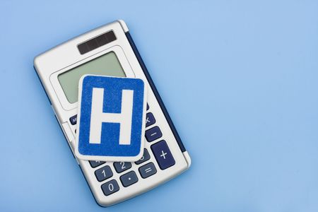 healthcare costs: A calculator and a hospital sign on a blue background, calculating healthcare costs Stock Photo