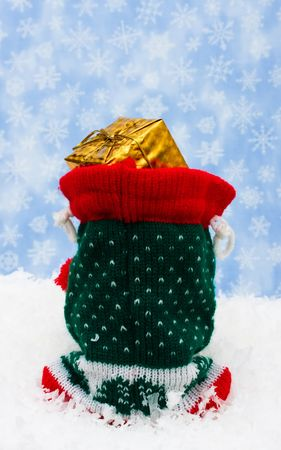 sac: Santa's sac with presents sitting on snow with a sky background, happy holidays