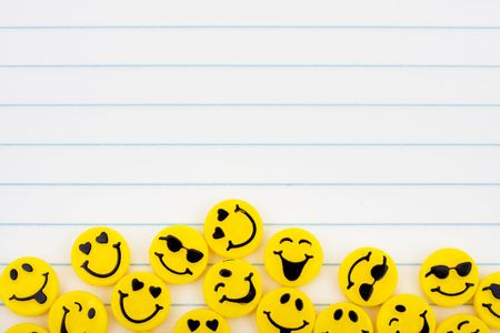 Lots of yellow smiley faces on a lined paper background, happy days photo