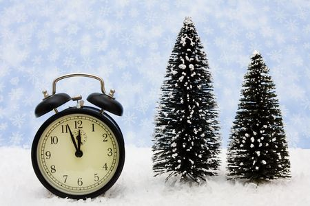 A black retro clock sitting on snow with a blue snowflake background, winter time photo