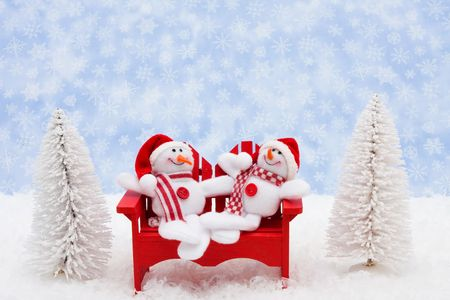 White evergreen trees sitting with a snowman on snow with a blue snowflake background, snowman photo