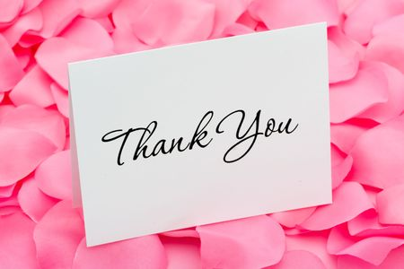 A thank you card sitting on a pink flower petal background, thank you with love photo