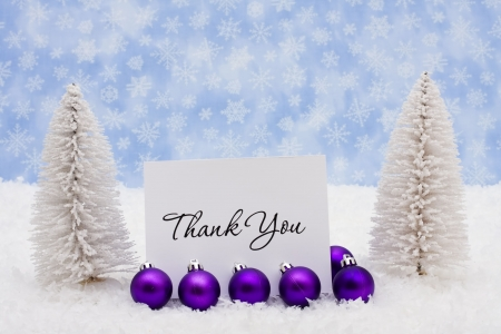 Evergreen trees sitting with purple glass Christmas balls and a thank you card on snow with a blue snowflake background