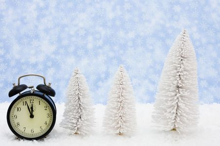 White evergreen trees sitting with a black retro clock on snow with a blue snowflake background, winter time photo
