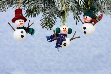 Snowmen ornaments hanging on a tree on a blue snowflake background photo