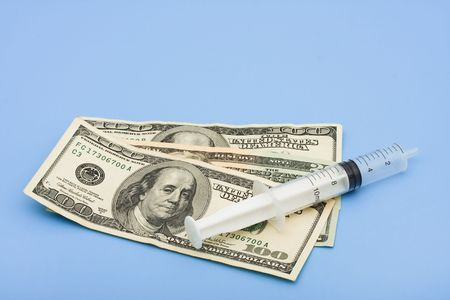 healthcare costs: Cash and a syringe on a blue background, healthcare costs Stock Photo
