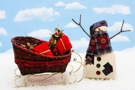 A snowman with presents in a sleigh on snow with a blue snowflake background photo