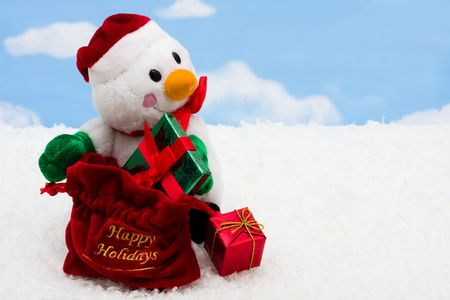 A snowman with presents on snow with a blue snowflake background photo