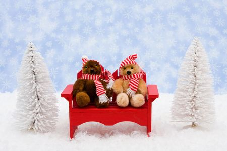 White evergreen trees sitting with teddy bears on snow with a blue snowflake background, winter bears photo