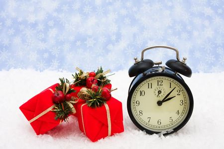 A black vintage face clock with presents sitting on snow background, Christmas time photo