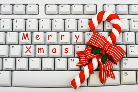 A keyboard saying Merry Xmas and a candy cane, Christmas shopping on the internet photo
