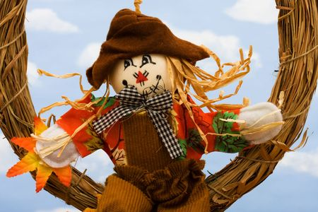 Fall leaves with a scarecrow on a sky background, fall border