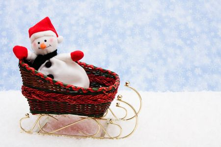 A snowman in a red sleigh on a blue snowflake background, snowman photo