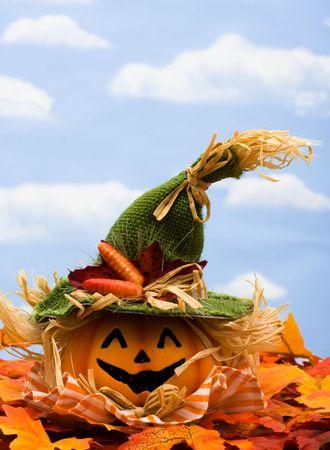 Fall leaves with a jack o lantern on a sky background photo