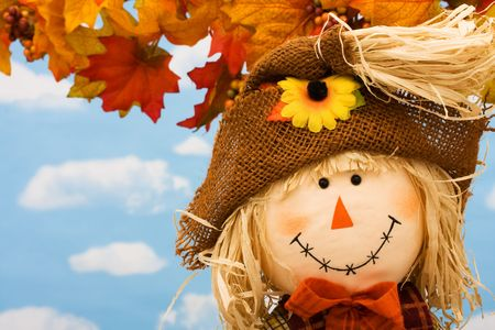 A scarecrow sitting on fall leaves on a sky background, scarecrow Banco de Imagens