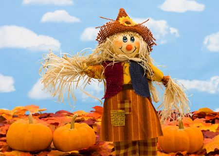 Fall leaves with a scarecrow and a gourd on a sky background, fall border photo