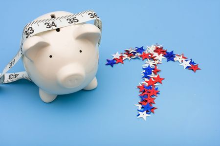 Piggy bank with measuring tape and multi coloured stars making an arrow on blue background, piggy bank, photo