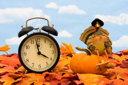 gourd: Fall leaves with a clock a turkey and a gourd on a sky background Stock Photo