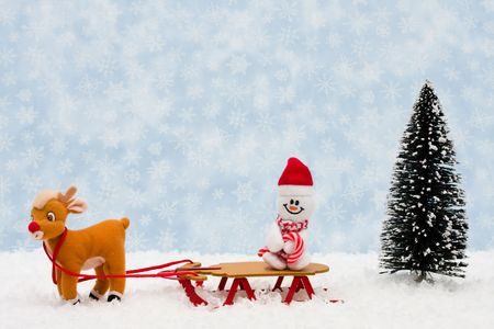 Evergreen trees sitting with a wooden sleigh with a blue snowflake background, Winter time photo