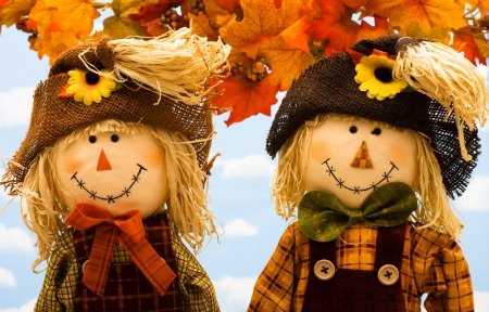 Fall leaves with a scarecrow  on a sky background, fall scene photo