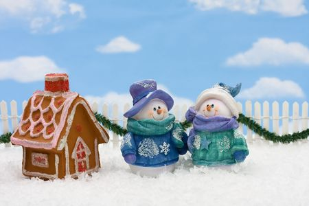 Gingerbread house on snow with a snowman and sky background, gingerbread house photo