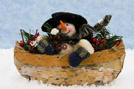 A Snowman sitting in a wooden bowl on a blue snowflake background, snowman photo