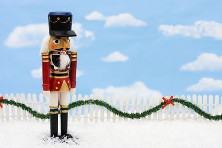 A nutcracker with a white picket fence with garland on a  sky background, Nutcracker Stock Photo - 5873267