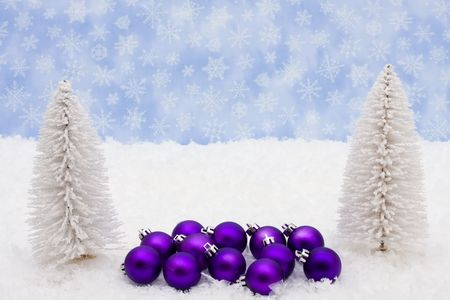 Evergreen trees sitting with purple glass Christmas balls on snow with a blue snowflake background, Christmas balls photo