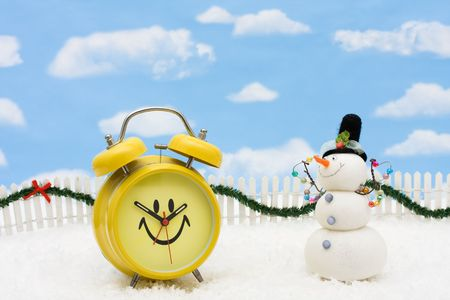 smiley: A yellow smiley face clock on a white picket fence with garland on a  sky background, winter time Stock Photo