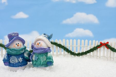 Two snowmen on a white picket fence with garland on a  sky background, gingerbread house Stock Photo - 5879038