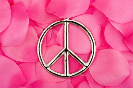 symbol of peace: A peace symbol sitting on a pink flower petal background, peace symbol