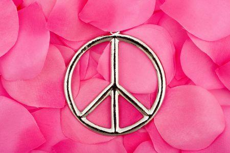 simbolo paz: Un s�mbolo de paz, sentado sobre un fondo de p�talos de flor rosa, s�mbolo de paz Foto de archivo