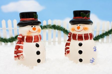 A snowman on a white picket fence with garland on a  sky background, winter scene photo