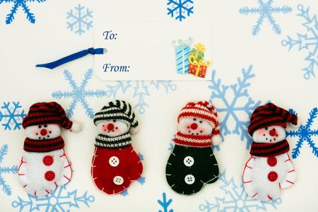Four snowman  mittens sitting together with a blank gift tag on a snowflake background, happy holidays photo