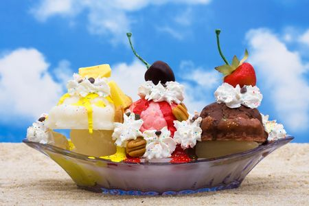 A banana split ice cream sitting on sand with a sky background Stock Photo